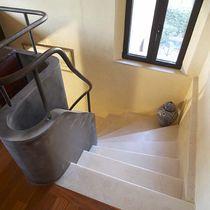 Escalera en L / con peldaños de piedra / estructura de acero / con contrahuella
