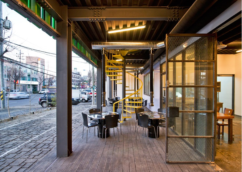 los paneles verdes plegables animan la fachada del restaurante de la casa del bosque de jya