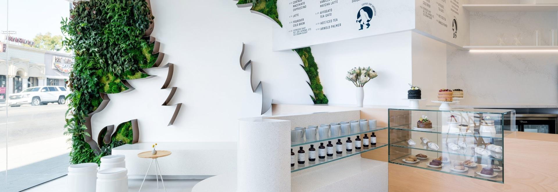 Los 11 pies Sasquatch rodeado por una pared verde acogen con satisfacción a clientes a esta cafetería