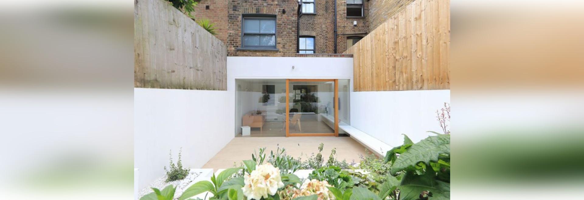 Una extensión blanca brillante del comedor y un jardín colgante ...