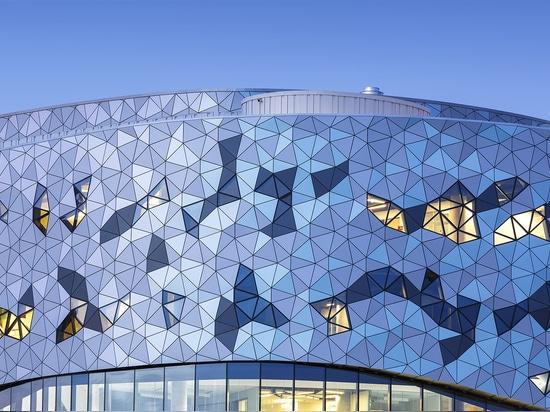 Del exterior, una fachada de cristal tessealted basada en un algoritmo matemático, triángulo-basado refleja la luz y modelos nefeloides lentamente de deriva en los espacios interiores