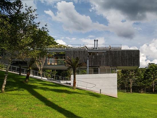 la casa brasileña rural por arquitetos del una es una composición de volúmenes que entrelazan