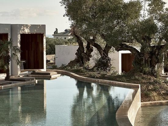 Un hotel en Grecia por block722 rodea un lago sereno, artificial