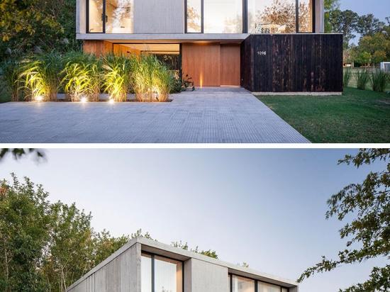 El piso inferior de esta casa del hormigón y de madera está casi totalmente abierto al exterior