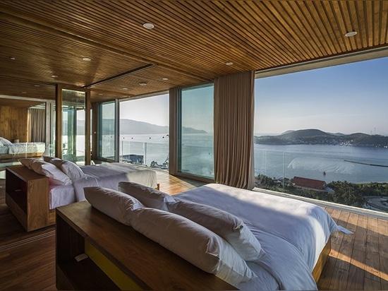 El chalet de los arquitectos de MM++ en Vietnam utiliza la logia de cristal retractable para la vista al mar única