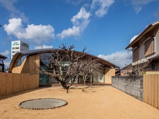el tejado de madera curvado del enrejado cuelga sobre la guardería del cielo azul de los nasca en Japón