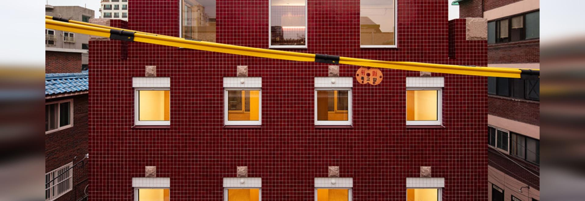 Aoa Architects utiliza baldosas de mármol rojo para revestir este apartamento en un barrio de Corea del Sur