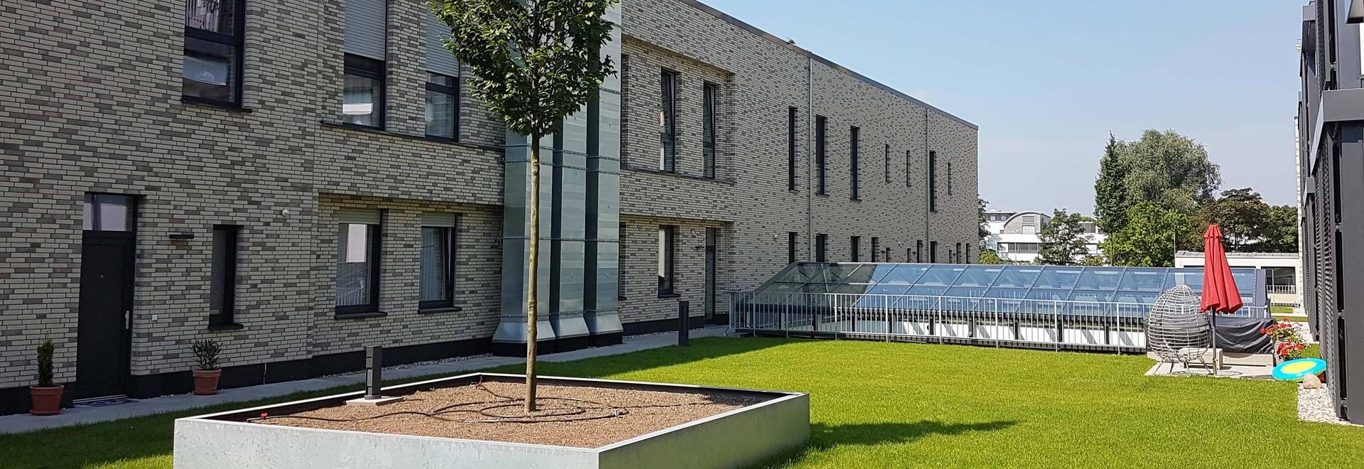 Hoy en día, los antiguos grandes almacenes Hertie en Lünen son una moderna propiedad residencial y comercial con 850 m² de patio de recreo y césped para tomar el sol en medio del tejado. © GRÜN+DAC...