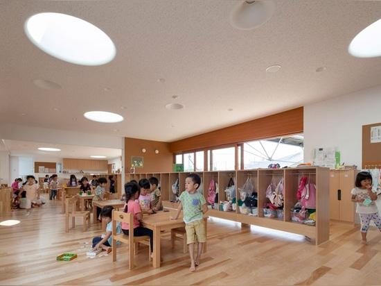 el taller de los arquitectos del aisaka organiza el cuarto de niños japonés alrededor de patio herboso