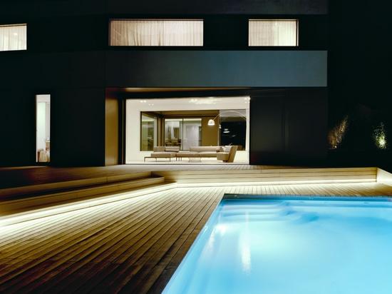 terraza de madera del natur del pur que enmarca un chalet con la piscina