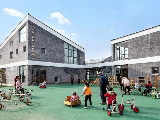 kindergarten en china rural organizado como un'mini pueblo' de volúmenes dispersos