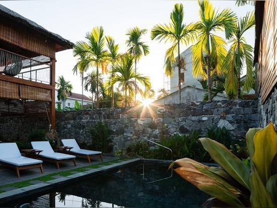 D1 construye una villa dúplex en Vietnam con materiales locales y techo de hoja de coco