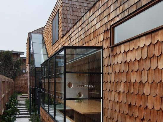 Esta nueva casa cubierta de tejas añade un encanto de madera a la calle
