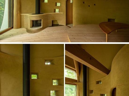 Una pequeña casa con forma de concha está rodeada por un bosque japonés