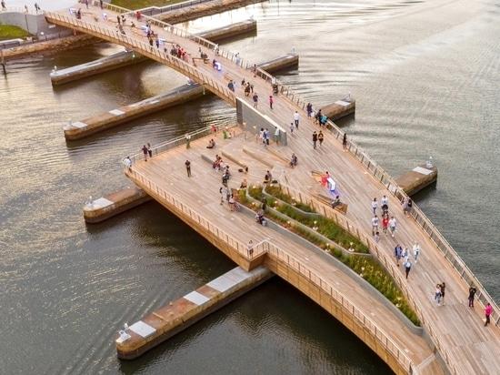 Un puente peatonal curvo une dos parques frente al río en Providence