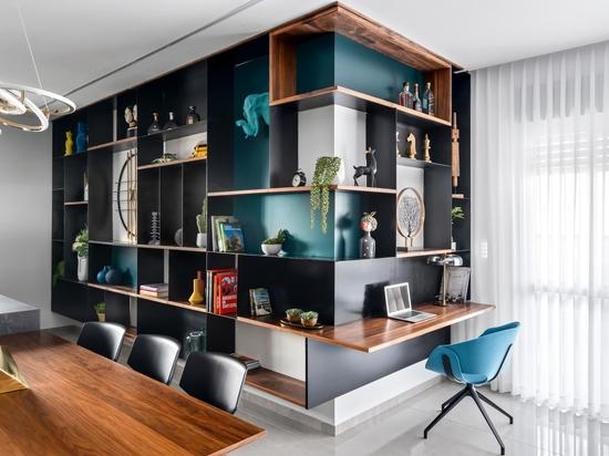 Un pequeño escritorio fue incluido en esta pared envolvente de estantería diseñada para mostrar piezas de decoración