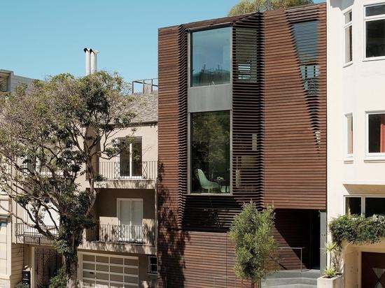 El exterior de madera de esta casa esconde una notable escalera azul en su interior