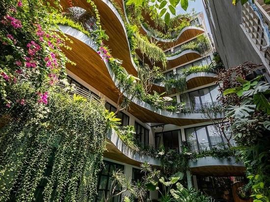 Los balcones ondulados con plantas colgantes son una característica de diseño en este edificio de apartamentos