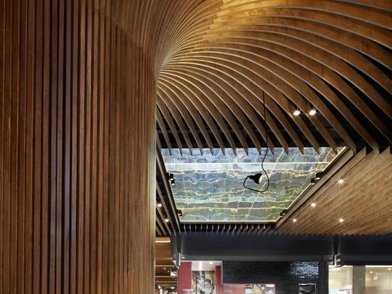 los perfiles de la madera crean los troncos de árbol textured y encubren las columnas estructurales